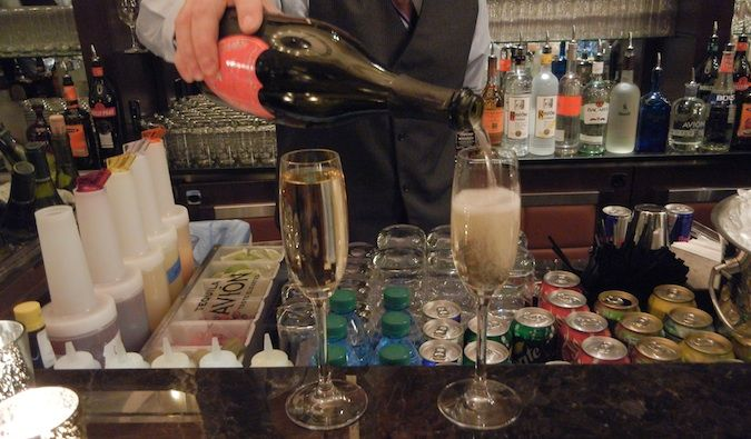 Bartender pouring two glasses of champagne at the bar for Sunday brunch in Vegas