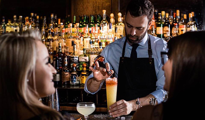 A bartender serves fancy cocktails to patrons at Death and Company in NYC