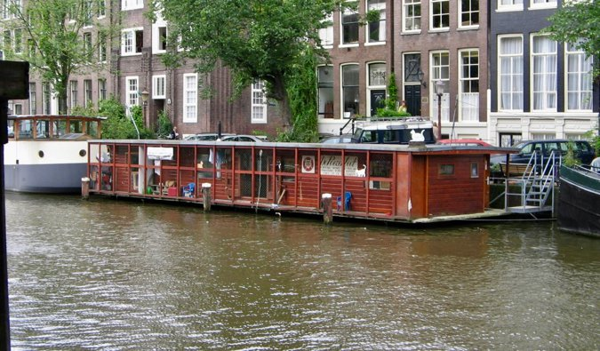 The red boat known as The Cat Boat floating on the water of the canal in Amsterdam