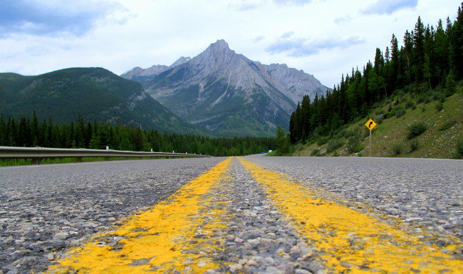Yellow road lines going in the direction of a distant mountain