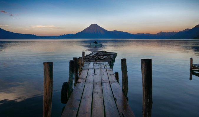An empty dock leading out to the water with a volcano in the background in Central America
