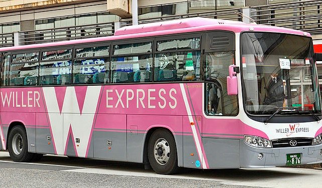 A pink Willer Express coach bus full of people in Japan