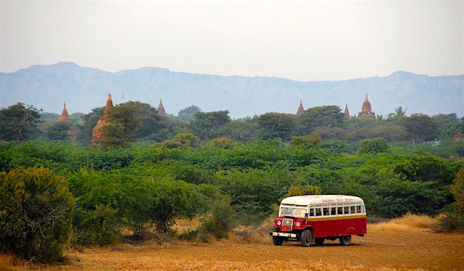 An old bus in thick foliage behind temples in Asia