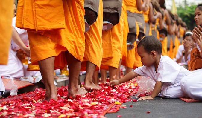 A child touching a bunch of rose petals that are laying at monks%image_alt%27 feet