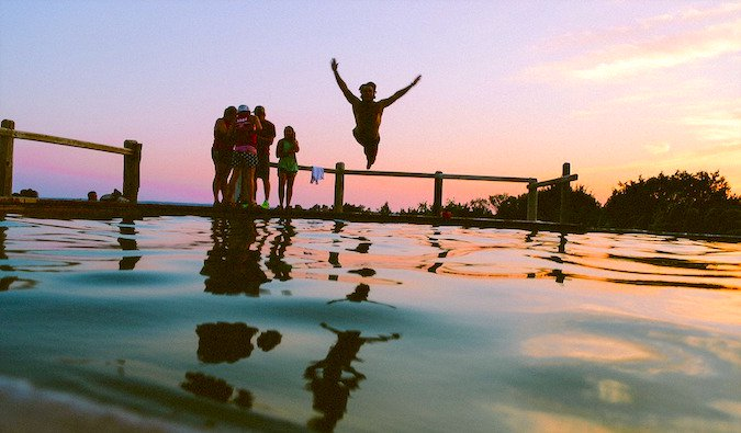 A group of travelers having fun jumping into water at sunset