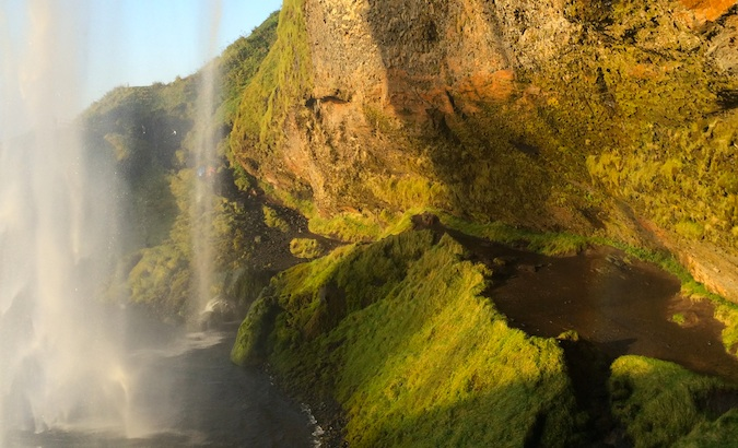 backside of Seljalandsfoss with excellent light, water, blue sky, and greenery