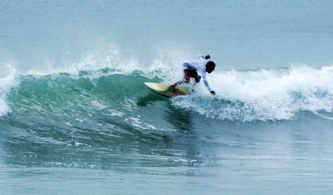 a person surfing at kuta beach in bali, indonesia