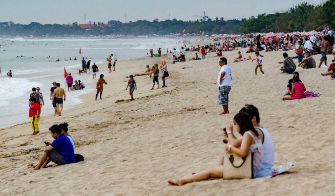 the crowded kuta beach in bali, indonesia