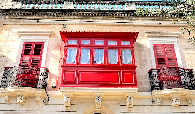 beautiful building facade and bright red shutters in malta
