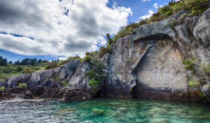 A Maori mural carved into stone near the water in New Zealand