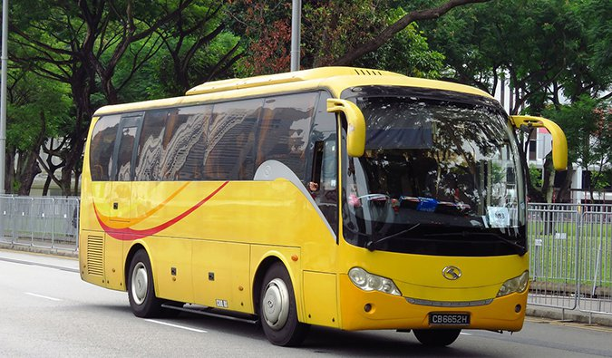 a yellow tourist coach bus in Southeast Asia
