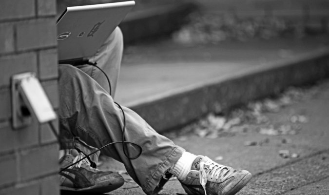 Traveler plugging laptop into a public outlet outside, bad cyber security practice